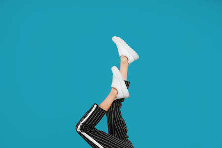 Woman in stylish sport shoes on light blue background Archivio Fotografico - 129798747