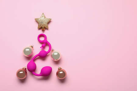 Christmas tree made with decorative balls, star and sex toy on pink background, flat lay. Space for text Archivio Fotografico - 129798754