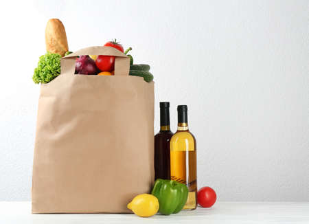 Shopping paper bag with different groceries on table against white background. Space for text