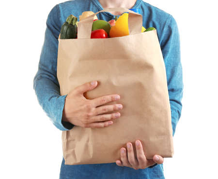 Man holding paper bag with different groceries on white background, closeup view