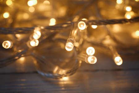 Glowing Christmas lights on white wooden background, closeup Фото со стока