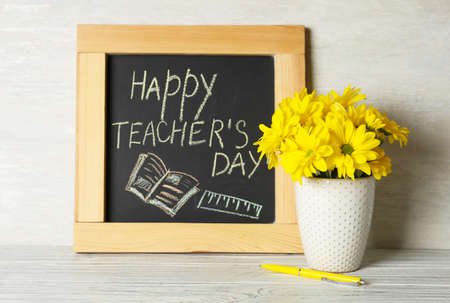 Chalkboard with inscription HAPPY TEACHERS DAY and vase of flowers on wooden table against light wall