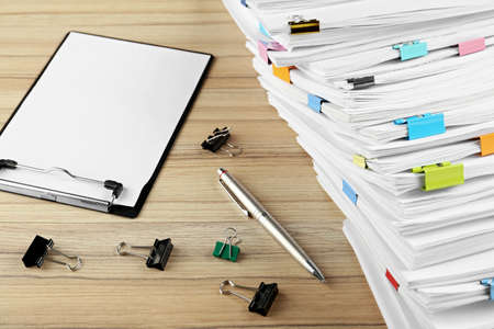Stack of documents with binder clips, clipboard and pen on wooden table 版權商用圖片