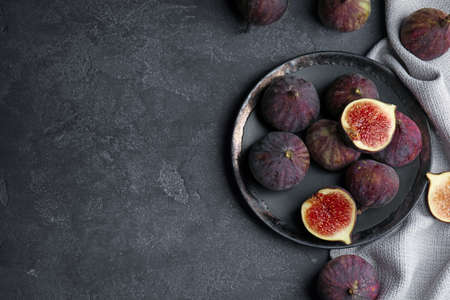 Tasty ripe fig fruits on grey table, flat lay. Space for text