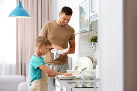 Dad and son wiping dishes in kitchen Stock Photo