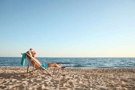 Young man relaxing in deck chair on beach near sea 版權商用圖片