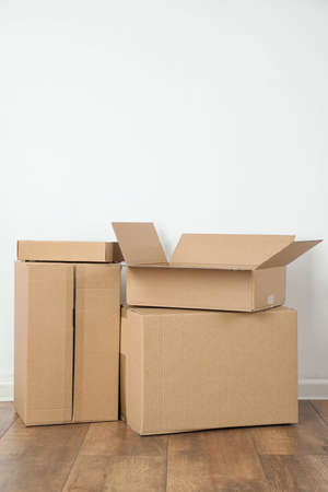 Pile of cardboard boxes near white wall indoors. Space for text Standard-Bild - 129807111