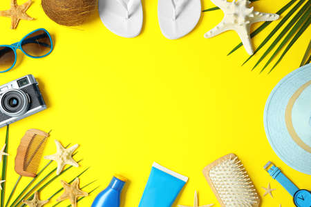 Flat lay composition with beach accessories on yellow background, space for text 스톡 콘텐츠