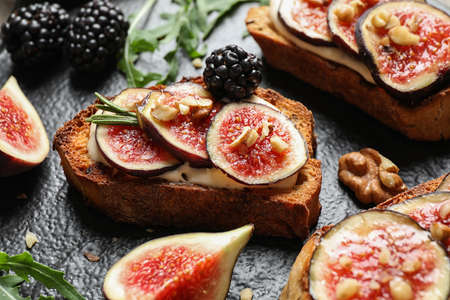 Bruschettas with cream cheese, figs and blackberries on slate plate, closeup Stock Photo