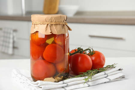 Pickled tomatoes in glass jar on white table in kitchen