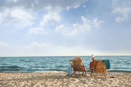 Young couple relaxing in deck chairs on beach near sea 写真素材