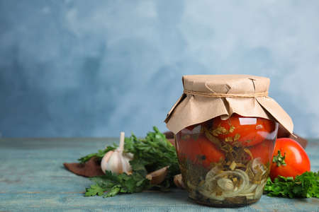Pickled tomatoes in glass jar and products on blue wooden table, space for text