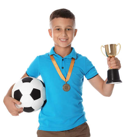 Happy boy with golden winning cup, medal and soccer ball on white background