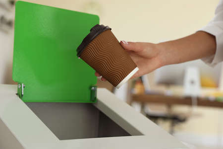 Woman throwing coffee cup into recycling bin at office, closeup Imagens