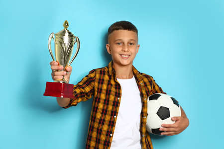 Happy boy with golden winning cup and soccer ball on blue background
