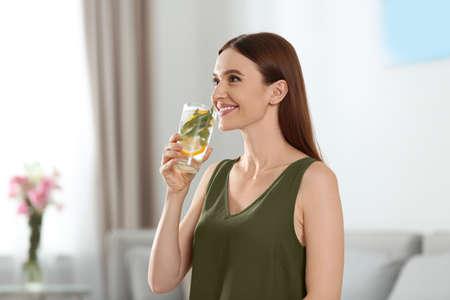 Jonge vrouw met limonade thuis. Verfrissend drankje