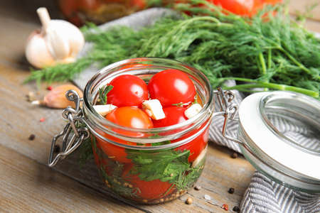Pickled tomatoes in glass jar and products on wooden table