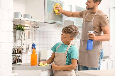 Dad and son cleaning in kitchen together Stock Photo