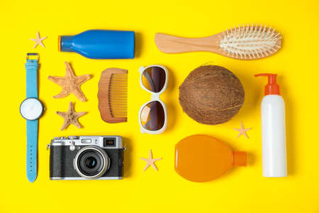 Flat lay composition with beach accessories on yellow background 스톡 콘텐츠