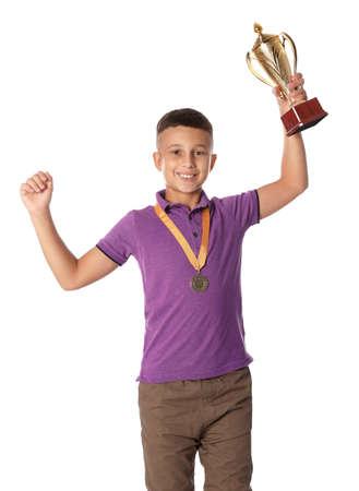 Ragazzo felice con la coppa e la medaglia d'oro vincenti su sfondo bianco