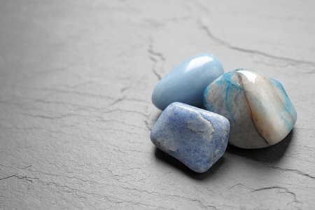 Blue gemstones on grey table, space for text 写真素材