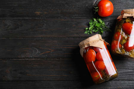 Flat lay composition with pickled tomatoes in glass jars on black wooden table, space for text