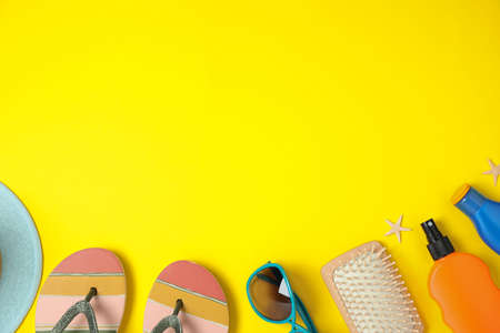 Flat lay composition with beach accessories on yellow background, space for text Reklamní fotografie - 129791454