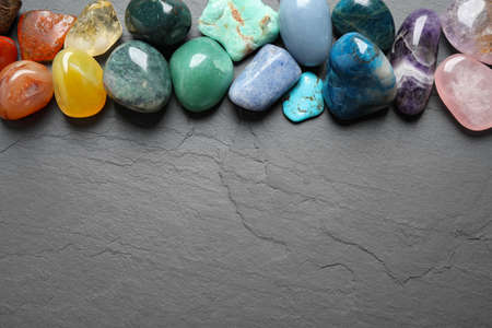 Flat lay composition with different gemstones on grey table, space for text