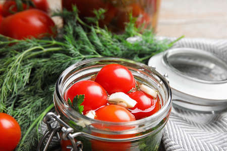 Pickled tomatoes in glass jar and products on table, closeup view