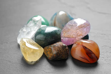 Pile of different beautiful gemstones on grey background