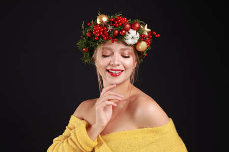 Beautiful young woman wearing Christmas wreath on black background