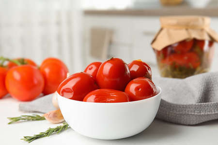 Pickled tomatoes in bowl near glass jar on white kitchen table