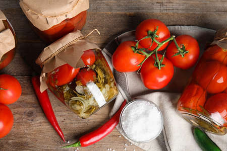 Flat lay composition with pickled tomatoes in glass jars on wooden table Фото со стока