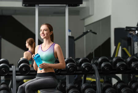 Athletic young woman with protein shake in gym