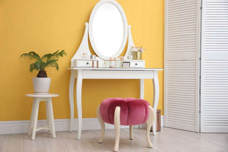 Stylish room interior with modern dressing table near yellow wall
