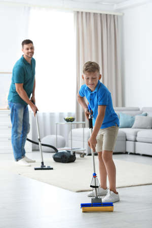 Dad and son cleaning living room together Фото со стока