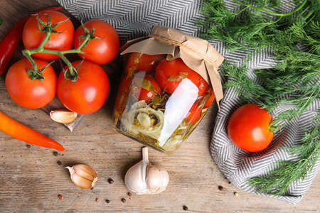 Flat lay composition with pickled tomatoes in glass jar on wooden table