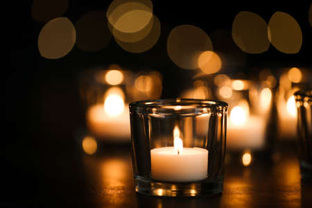 Burning candle on table against blurred background. Funeral symbol