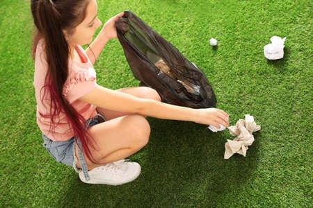 Mädchen, das draußen Müll aufhebt. Recyclingkonzept Standard-Bild