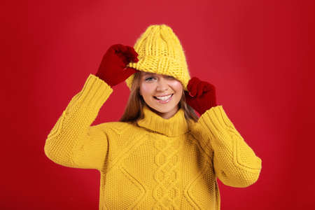 Funny young woman in warm sweater, gloves and hat on red background. Winter season