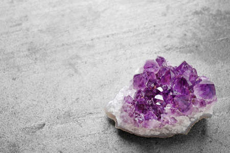 Beautiful purple amethyst gemstone on grey table, space for text Stok Fotoğraf