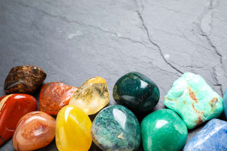 Different gemstones on grey table, closeup. Space for text