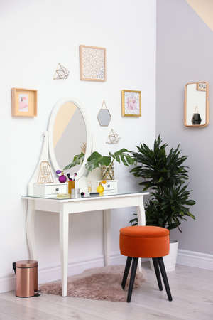 Stylish room interior with modern dressing table near light wall Stock Photo