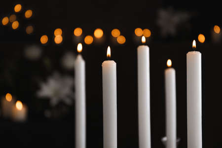 Burning candles on blurred background. Funeral symbol