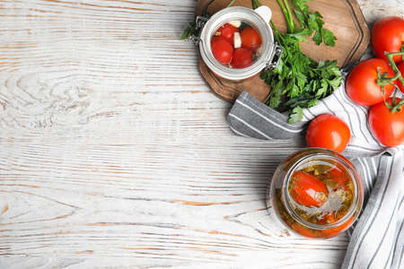 Flat lay composition with pickled tomatoes in glass jars on white wooden table, space for text Stok Fotoğraf