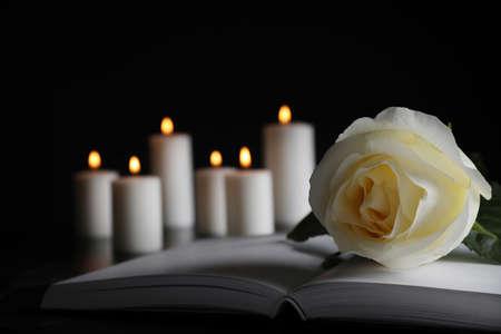 Weiße Rose, Buch und verschwommene brennende Kerzen auf dem Tisch in der Dunkelheit, Nahaufnahme mit Platz für Text. Begräbnissymbol
