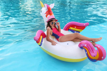 Happy cute girl on inflatable unicorn in swimming pool