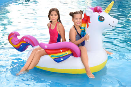 Happy girls on inflatable unicorn in swimming pool 免版税图像