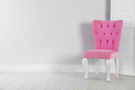 Stylish pink chair and folding screen near white wall. Space for text 版權商用圖片