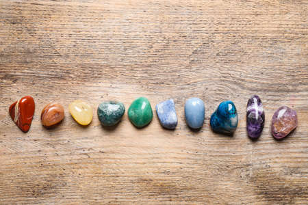 Flat lay composition with different gemstones on wooden table Stock Photo